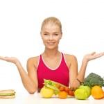 Woman with fruits and hamburger — Stock Photo #24011049