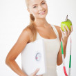 Sporty woman with scale, apple and measuring tape — Stock Photo #24011069