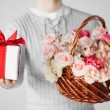 Man holding basket full of flowers and gift box — Stock Photo