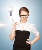 Woman pointing her finger at light bulb — Foto de Stock