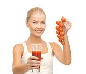 Mujer sosteniendo el vaso de jugo y tomate — Foto de Stock