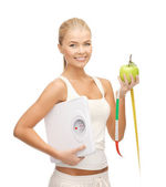 Sporty woman with scale, apple and measuring tape — Stock Photo