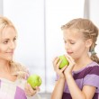 Mother and little girl with green apple — Stock Photo #24368133