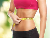 Trained belly with measuring tape — Stock Photo