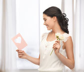 Young woman holding flower and postcard — Foto de Stock