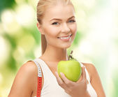 Sporty woman with apple and measuring tape — Stock Photo