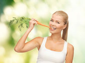 Healthy young woman biting carrot — Stockfoto