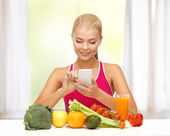 Woman with fruits, vegetables and smartphone — Stok fotoğraf