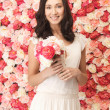 Woman with bouquet and background full of roses — Photo
