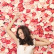 Beautiful woman and background full of roses — Stock Photo
