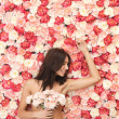 Woman and background full of roses — Stock Photo
