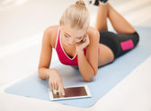 Woman lying on the floor with tablet pc — Stock Photo