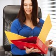 Young businesswoman with folders sitting in chair — Stock Photo #25009727