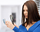 Woman with magnifying glass and euro cash money — Stock Photo