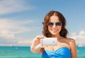 Woman in bikini with phone — Stock Photo