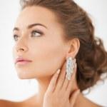 Woman wearing shiny diamond earrings — Stock Photo #25108249