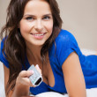 Woman with TV remote — Stock Photo