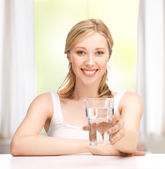 Young smiling woman with glass of water — Stockfoto