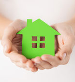 Woman hands holding green house — Foto Stock