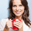 Smiling woman with red cup — Stock Photo