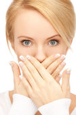 Amazed woman with hand over mouth — Stock Photo