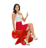 Woman sitting on big red percent sign — Stock Photo