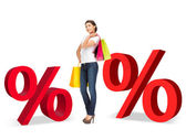 Woman with shopping bags and percent signs — Stock Photo
