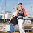 Young couple in duty free shopping bags — Stock Photo #25761575
