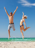 Couple jumping on the beach — Stock Photo