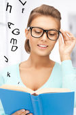Woman in glasses reading book — ストック写真