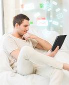 Homem sentado no sofá com o tablet pc — Fotografia Stock