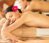 Couple in spa with hot stones — Stock Photo