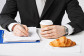 Businessman with coffee writing something — Stock Photo