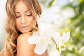 Beautiful woman with orchid flower — Stockfoto