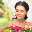 Housewife with flower in pot and watering can — Stock Photo