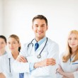 Male doctor in front of medical group — Stock Photo #26681721