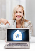 Woman with laptop pointing at email sign — Stock Photo