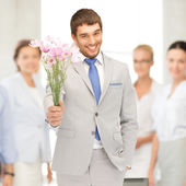 Handsome man with flowers in hand — Stock Photo