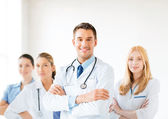 Male doctor in front of medical group — Stock Photo