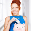 Woman putting cash money into piggy bank — ストック写真
