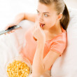 Woman watching tv and eating popcorn — Stock Photo