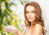 Gül yaprakları ile güzel bir kadın — Stok fotoğraf