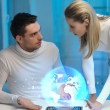 Futuristic man and woman with globe hologram — Stock Photo