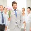 Handsome man with flowers in hand — Stock Photo #27050625