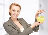 Woman putting cash money into small piggy bank — Stock Photo