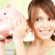 Lovely girl with big piggy bank — Stock Photo #27095873