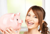 Lovely girl with big piggy bank — Stock Photo