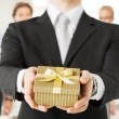 Foto Stock: Man hands holding gift box in office