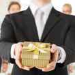 Man hands holding gift box in office — Foto de Stock