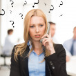 Confused woman with phone in office — Stock Photo